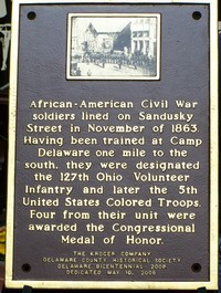 Plaque on the east side of Sandusky Street Dedication of Wall Plaque Honoring Civil War Troops Trained at Camp Delaware 'Camp Delaware' USCT Commemoration Dedicated to the 127th Ohio Voluntary Infantry Regiment of colored soldiers who were trained at Camp Delaware. A famous photograph of the soldiers shown lined up in Sandusky Street in 1864, reproduced on the plaque. The regiment was subsequently redesignated the 5th United States Colored Infantry Regiment