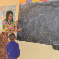 One of the students, Praygod, learns the alphabet from Thomas' teaching