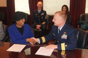 HU Executive Vice President and Provost Dr. JoAnn Haysbert and Rear Admiral David Throop shake hands after signing the agreement.