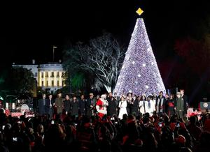 Rev. Haggins on stage singing with President Barack Obama, First Lady Michelle Obama, Santa and others during the ceremony.  (AP Photo/ Alex Brandon)