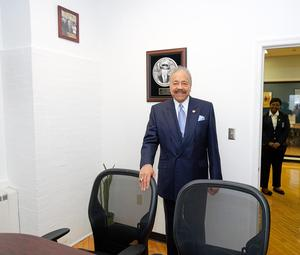 Dr. Harvey poses in front of the plaque in the conference room dedicated to his father, W.D.C. Harvey