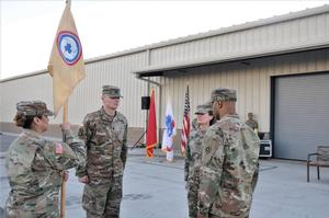 311th ESC Commanding General, Brigadier. General Dianne Del Rosso (second from right), incoming HHC 311th ESC Commander, CPT. Michael Ashburn (right), 1st. Sgt. Leticia Mendez (left), and outgoing HHC Commander, CPT Guy Bester, prepare to pass the guidon signifying the change of command leadership at the HHC 311th ESC.