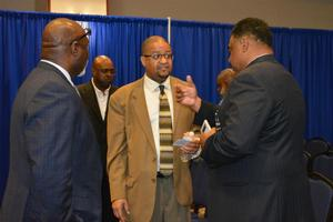 Mr. James F. Harris speaking with attendees of the Symposium