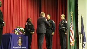 Chief Terry Sult pins the Lifesaving Medal on Officer Deherrara's uniform.