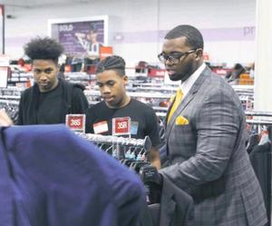 Andre Jones helping high school students shop for suits